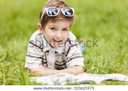 Beauty smiling child boy in sunglasses reading book outdoor on green grass field - stock photo
