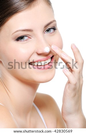 Beauty smiling female face with drop of  cosmetic cream on her nose - stock photo