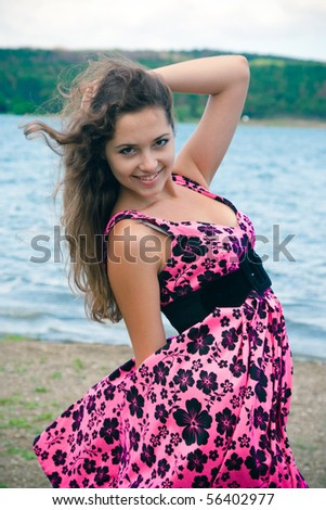 Beauty smiling girl in a pink dress near the lake