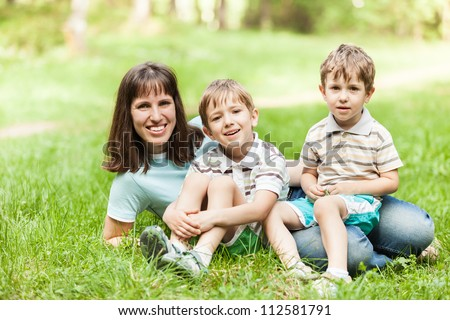 Beauty smiling mother and little sons walking outdoor on green grass field
