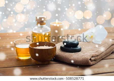 beauty, spa, bodycare, natural cosmetics and concept - himalayan pink salt with massage oil and bath towel on wooden table over lights and snow