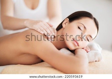 beauty, spa, resort and relaxation concept - beautiful woman in spa salon getting massage - stock photo