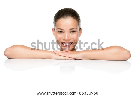 Beauty. Spa skin care woman smiling happy leaning face and arms on white blank copy space or edge. Beautiful mixed race Asian Caucasian female model isolated on white background. - stock photo