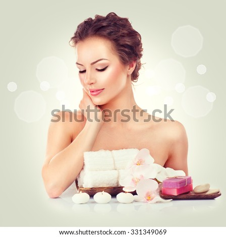 Beauty Spa Woman touching her soft skin, Beautiful girl portrait. Day spa, wellbeing concept. Handmade soap bars, towels, candles and orchid flowers on her table - stock photo