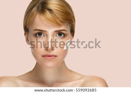 Beauty Spa Woman with perfect skin Portrait. Beautiful Blonde Red Hair Spa Girl showing empty copy space  for text. Proposing a product. Gestures for advertisement. Beige Pink background
