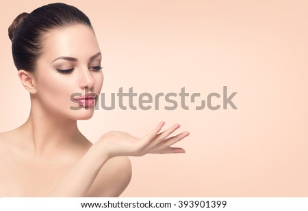 Beauty Spa Woman with perfect skin Portrait. Beautiful Brunette Spa Girl showing empty copy space on the open hand palm for text. Proposing a product. Gestures for advertisement. Beige background - stock photo