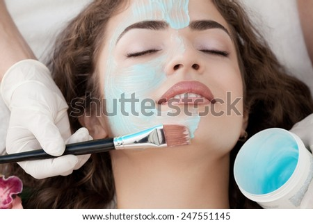 Beauty spa: Young Beautiful Relaxing Woman Having Moistening Mask Applied . - stock photo