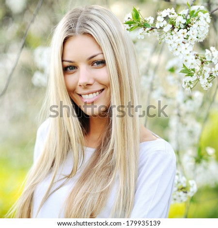 Beauty spring girl portrait over blooming tree with flowers - stock photo