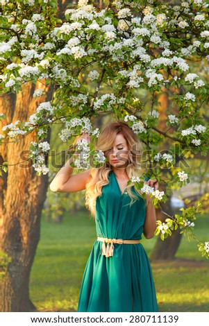 beauty spring girl portrait over blooming tree with flowers,beautiful girl in the apple blossoms. - stock photo