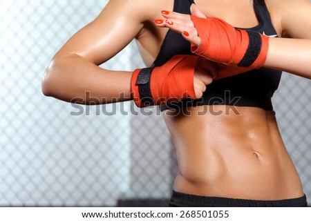 Beauty strikes. Close-up of a woman doing boxing bandages in a fighting cage - stock photo
