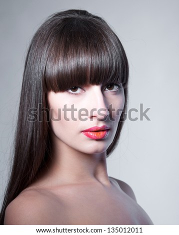 Beauty studio portrait of beautiful woman model with long straight fringe, natural makeup, bright colorful red glossy lips, looking at camera. Gray background, copy space