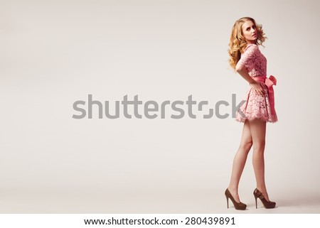 Beauty studio portrait of girl in pink dress with wavy hairs - stock photo