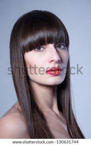 Beauty studio portrait of pretty young woman model with straight hair, long straight fringe, natural makeup, bright colorful red glossy lips half open, looking at camera. Gray background, copy space
