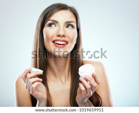 Beauty style face portrait of young woman holding open container of skin care cream.