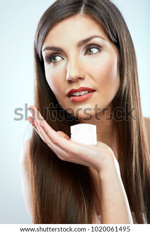 Beauty style face portrait of young woman holding skin care cream. Isolated studio portrait.