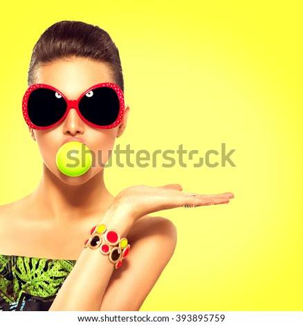 Beauty summer fashion model girl wearing sunglasses with green bubble of chewing gum and bright makeup showing empty copy space on the open hand palm for text over yellow background. Beautiful woman - stock photo