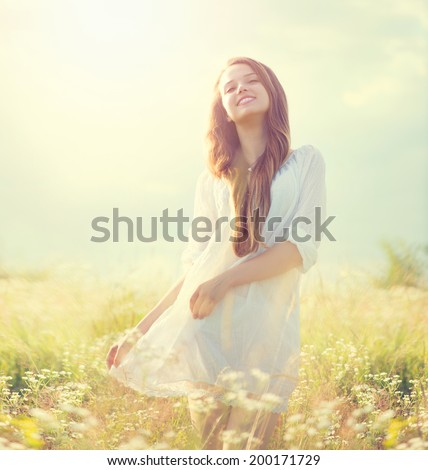 Beauty Summer Girl Outdoors enjoying nature. Beautiful Teenage Model girl in white dress on a Field with blooming wild flowers, Sun Light. Free Happy Woman. Toned in warm colors - stock photo