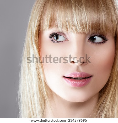 Beauty surprised blonde woman against gray background - stock photo