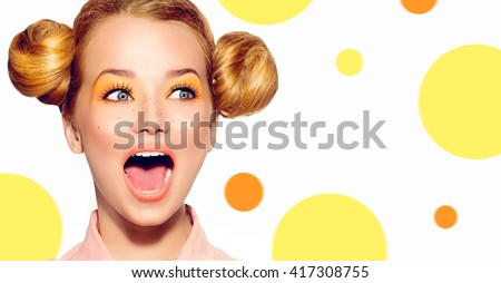 Beauty Surprised Teenager Model Girl. Beautiful Joyful teen girl with freckles, funny red hairstyle and yellow makeup on colorful background - stock photo