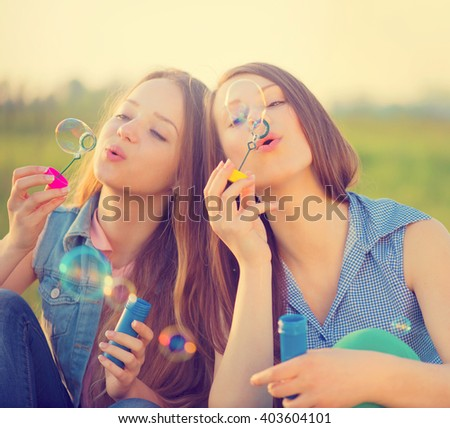 Beauty teen girls having fun outdoors. Beautiful joyful teenagers laughing and blowing soap bubbles in spring park. Girlfriends outdoor. Friendship - stock photo