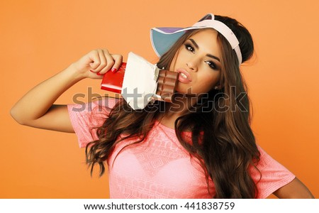 Beauty teen model girl eating dark chocolate. Beautiful Surprised young woman takes chocolate sweets,smiling and having fun. Funny girl, professional make up and bow hairstyle.  - stock photo