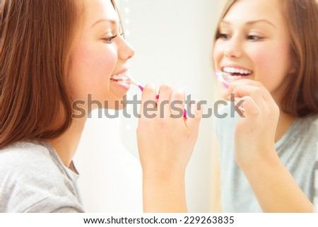 Beauty teenage girl brushing her teeth at home. Pretty young woman using a toothbrush, smiling at the mirror, enjoying beautiful white teeth. Healthcare of mouth, dental hygiene - stock photo