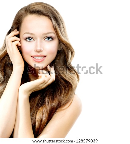 Beauty Teenage Girl Portrait isolated on a White Background. Beautiful Young Woman With Healthy Long Hair touching her Face. Smiling Pretty Teenager - stock photo