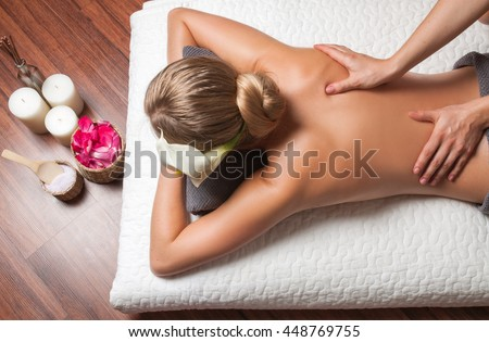 Beauty treatment concept. Beautiful young woman having massage with  in spa salon - stock photo