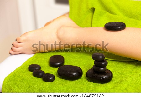 Beauty treatment concept. Woman relaxing getting spa hot stone therapy legs massage procedure in salon. Body care healthy lifestyle. - stock photo