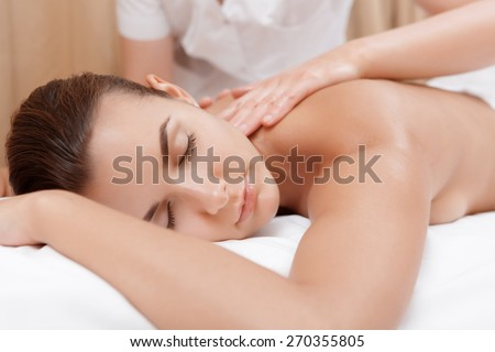 Beauty treatment. Young brunette getting back massage in spa salon - stock photo