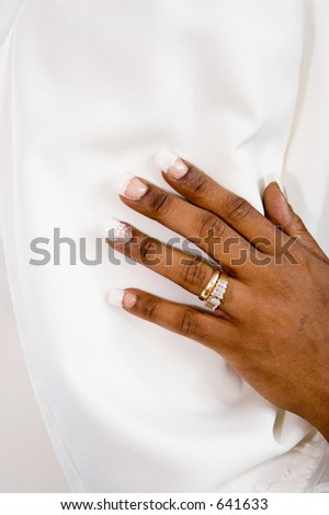 Beauty up-close as this bride's show her hand embracing her new husband's arm showing her wedding ring.