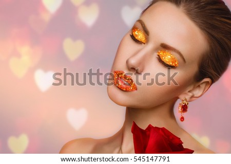 Beauty Valentine's Day. Gold makeup and manicure. Girl on the background blurry hearts. Luxury woman with gold earrings. Making Cards Valentine's day. A girl holding a red rose