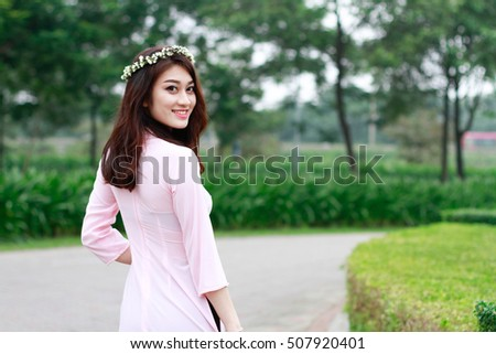 Beauty Vietnamese women wear traditional with flowers bouquet in the park.The Ao dai ( long-dress Vietnamese) is traditional costume of Vietnamese woman