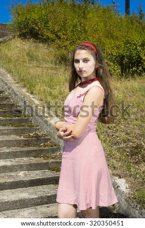 Beauty vintage teen Girl posing Outdoors at the stairs in Sun Light  with Blowing Long Hair.