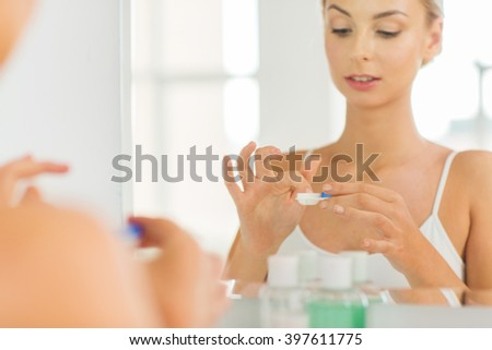 beauty, vision, eyesight, ophthalmology and people concept - close up of young woman applying contact lenses at mirror in home bathroom - stock photo