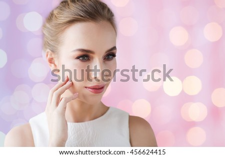 beauty, wedding and people concept - beautiful smiling woman in white dress touching her face over rose quartz and serenity lights background - stock photo