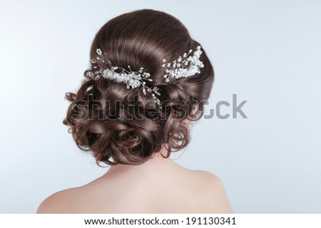 Beauty wedding hairstyle. Bride. Brunette girl with curly hair styling with barrette.  - stock photo