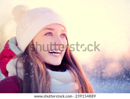 Beauty Winter Girl Blowing Snow in frosty winter Park. Outdoors. Flying Snowflakes. Sunny day. Backlit. Beauty young woman Having Fun in Winter Park. Good mood  - stock photo