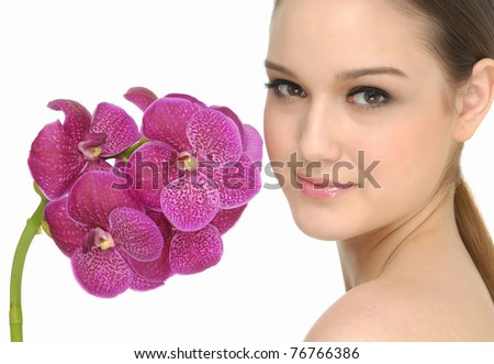 beauty with an orchid next to her face - stock photo