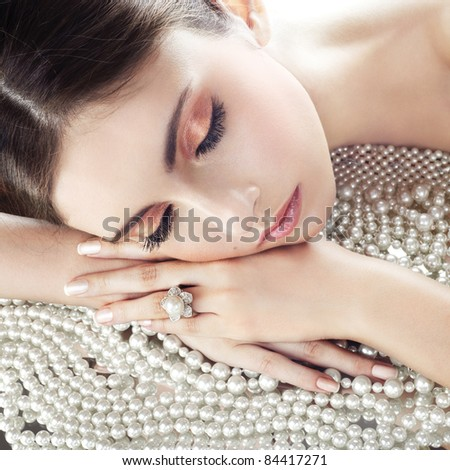 Beauty with diamond ring on pearls background - stock photo