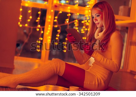 Beauty with digital tablet. Beautiful young woman in white sweater holding digital tablet while sitting on the floor at home with Christmas lights in the background - stock photo