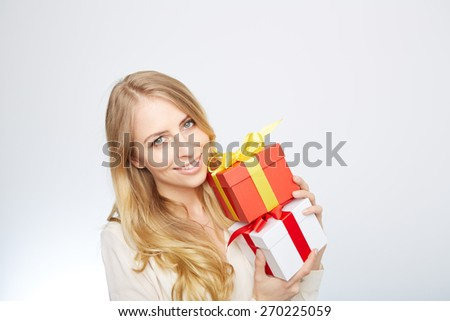 Beauty with gift box. Beautiful young blond hair woman holding gift box and smiling while standing isolated on white background