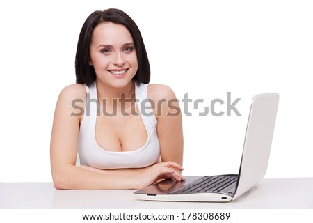 Beauty with laptop. Attractive young woman with beautiful cleavage working on laptop and smiling while sitting at the table and isolated on white