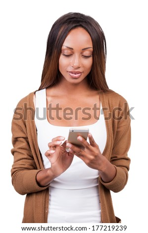 Beauty with mobile phone. Beautiful young African woman looking at her mobile phone and smiling while standing isolated on white  - stock photo