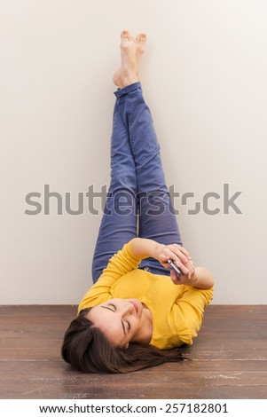 Beauty with mobile phone. Beautiful young woman holding mobile phone while lying on the floor and leaning her legs at the wall - stock photo