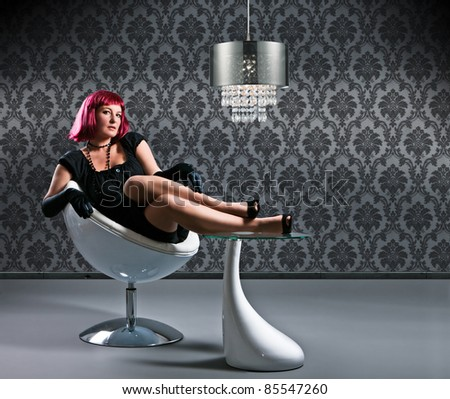 beauty with red hair in evening-dress sitting on a modern chair - stock photo