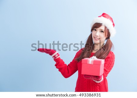 beauty woamn take gift and show something  in christmas isolated on blue background, asian