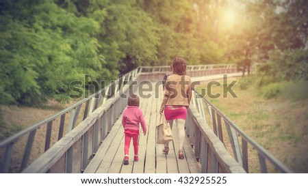 Beauty woman and her children walking on bridge a sunny day - stock photo