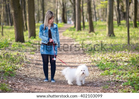 Beauty woman and her dog in the park a spring day