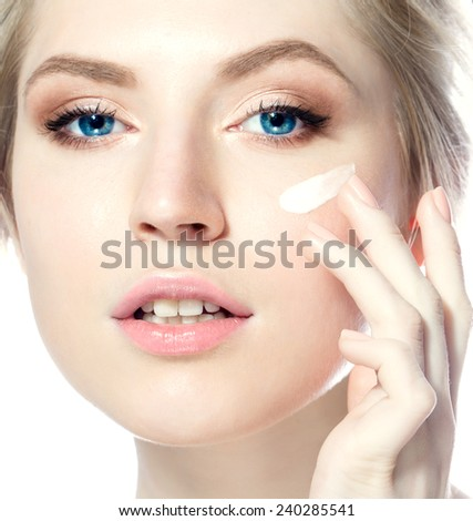 Beauty woman applying cream on her face - stock photo